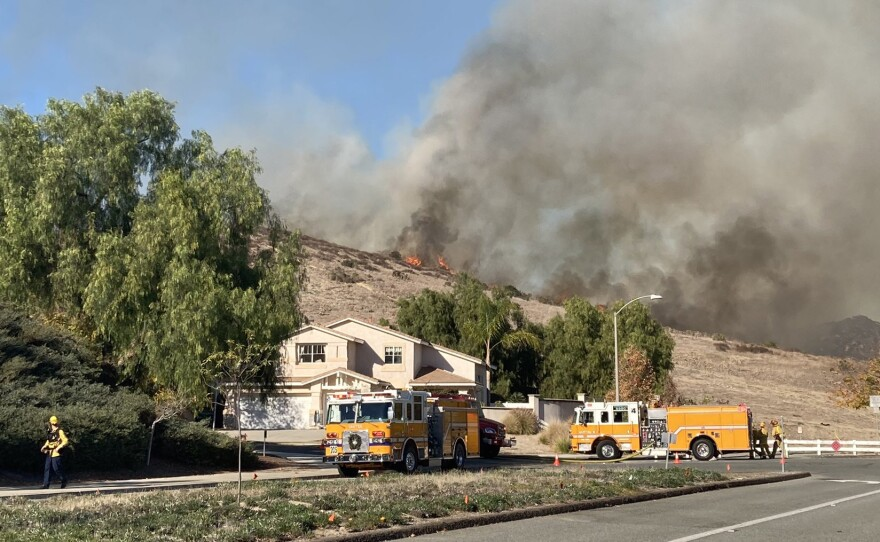 Flames are seen on the hillside in Santee at the Chaparral Fire on Dec. 16, 2020.