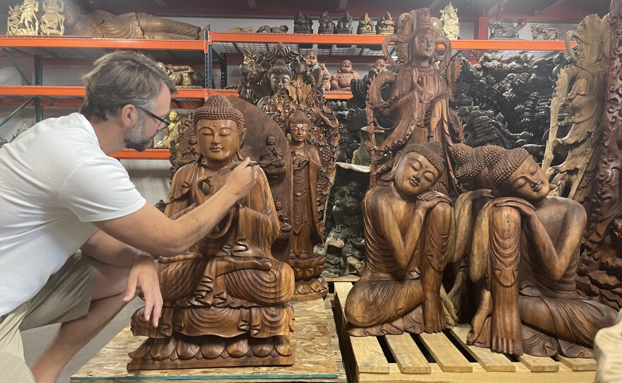 Kyle Tortora, the owner of Lotus Sculpture in Oceanside, brushes off a sculpture with a brush. July 1, 2021.