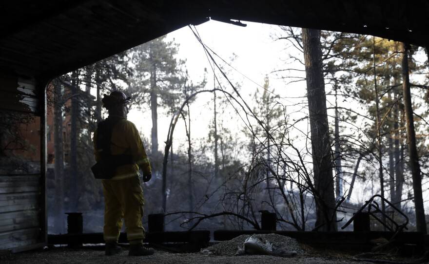 A firefighters looks out from inside a burned down property in Idyllwild, Calif., Thursday, July 26, 2018.