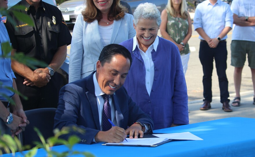 Council President Jennifer Campbell looks on as Mayor Todd Gloria signs two infrastructure bills at Mesa Verde Park in Mira Mesa, Aug. 12, 2021.