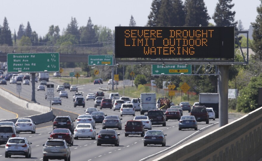 Motorists pass a sign on Highway 50 in Sacramento County's Rancho Cordova reminding them to reduce water use due to the statewide drought, April 2, 2015.