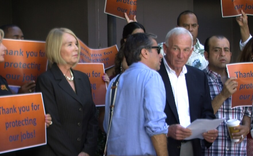 Jason Roe, a spokesman for the San Diego Small Business Coalition, talks to San Diego Regional Chamber of Commerce CEO Jerry Sanders at a news conference announcing the group has enough signatures to force a vote on the minimum wage increase, Sept. 16, 2014.