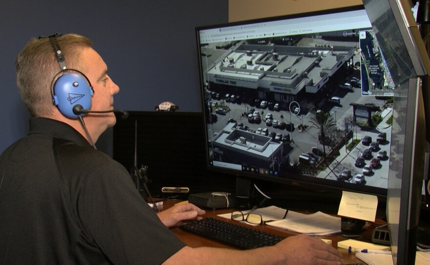 A man wearing headphones controls a Chula Vista Police Department drone from a computer while sitting at a desk, Feb 5. 2020.