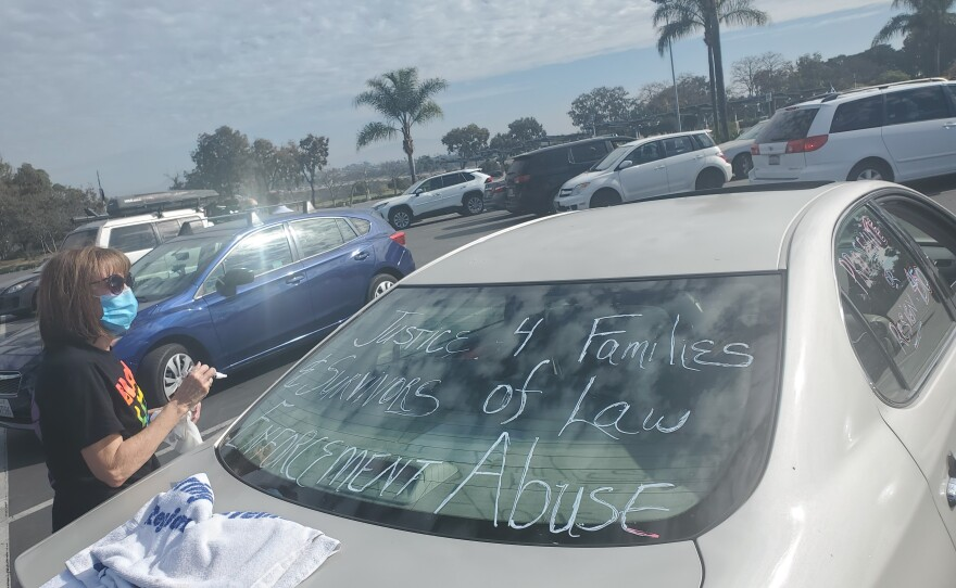 A woman decorates her car in the San Diego Zoo parking lot before a car caravan protest calling for justice in police shootings, Jan. 18, 2021.