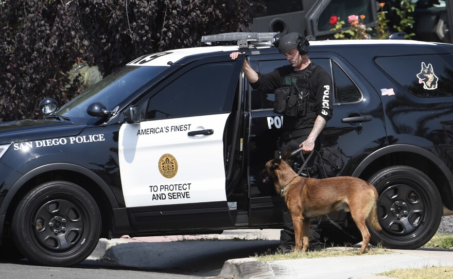 A San Diego police officer with a police dog waits outside a house with a possible suspect inside Friday, July 29, 2016.