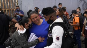 Lizeth Morales, left, of Honduras, and her son, Alex Cortillo, right, get a hug from Erika Valladares Ponce, center, as they wait to cross into the United States to begin the asylum process Monday, July 5, 2021, in Tijuana, Mexico.