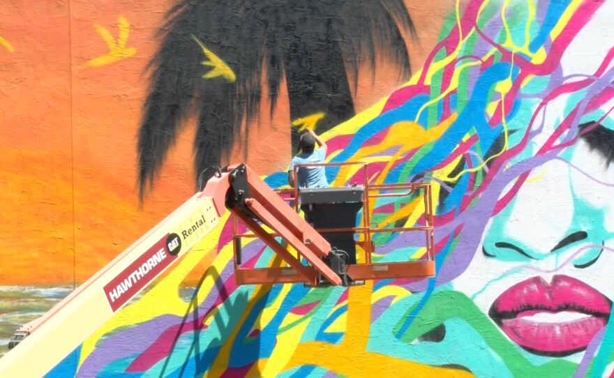 Mauro Alvarez, a local artist, stands on a lift and paints a bird on a mural at Interfaith's recuperative center in Escondido, June 10, 2021.