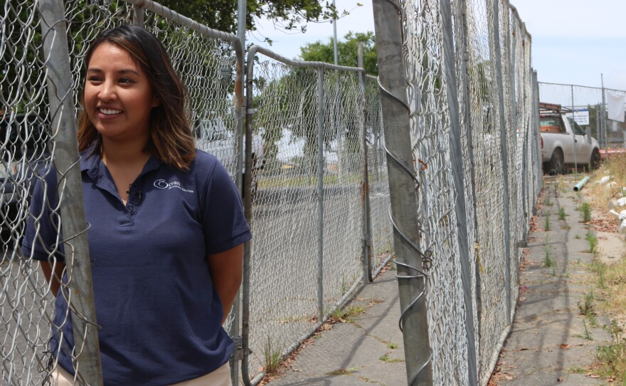 Ocean Discovery Institute Manager of Business Development Carla Pisbe Camacho stands near the chain link fence surrounding the organization's future Living Lab, April 24, 2017.