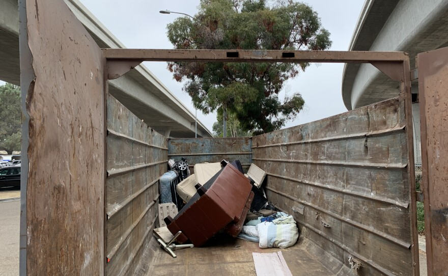 A dumpster with a pile of large household items during Caltrans collection event in San Diego County in 2020.