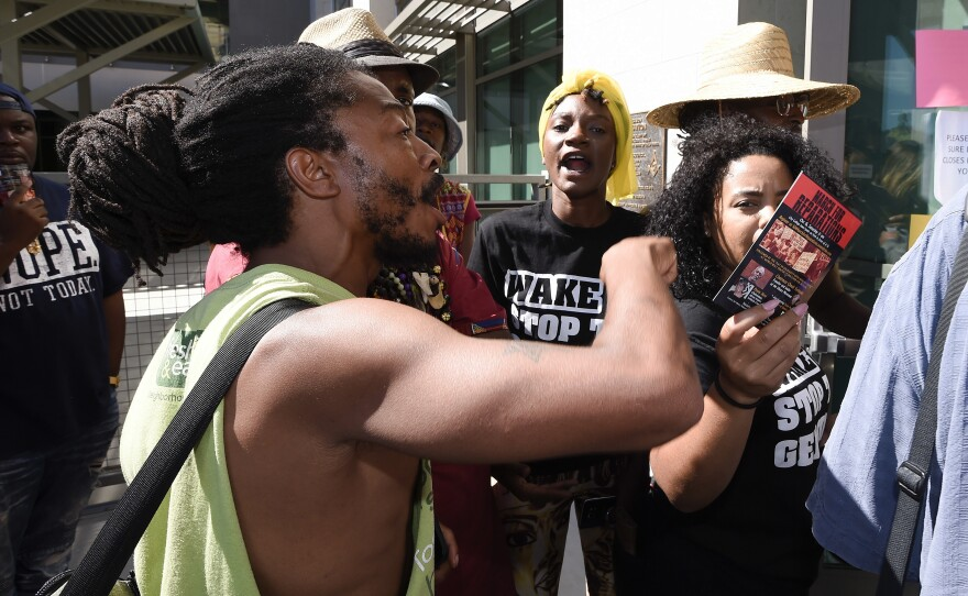 Protesters yell at police officers in front of the El Cajon Police Department headquarters before a news conference, Sept. 30, 2016.