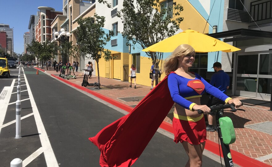 Comic-Con visitor Sapphire Nova rides an electric scooter down a protected bike lane on Sixth Avenue wearing a Supergirl costume, July 18, 2019.