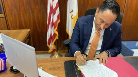 """Mayor Todd Gloria signs an ordinance to ban """"ghost guns"""" in the City of San Diego at his office in San Diego, Calif. Sept. 23, 2021."""