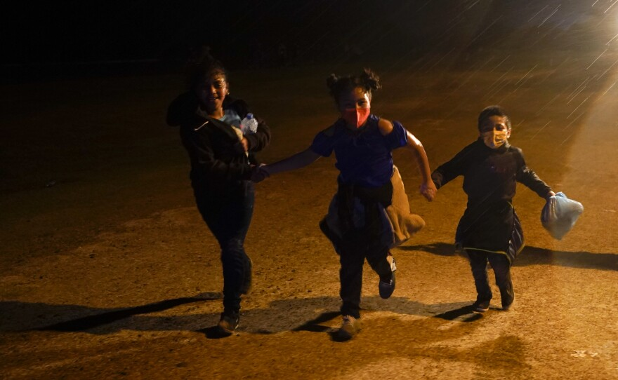 In this May 11, 2021 file photo three young migrants hold hands as they run in the rain at an intake area after turning themselves in upon crossing the U.S.-Mexico border in Roma, Texas.