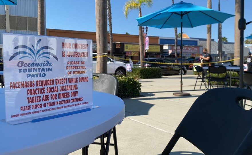 """""""Oceanside Fountain Patio"""" sign on table near the Oceanside Library with rules for the new open air patio available to diners. October 29, 2020"""