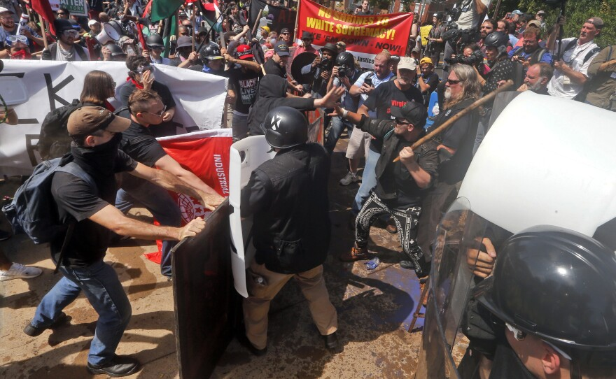 In this Aug. 12, 2017 file photo, white nationalist demonstrators clash with counter-demonstrators at the entrance to Lee Park in Charlottesville, Va.