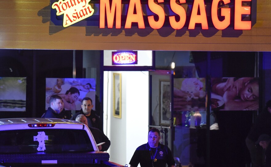 Authorities investigate a fatal shooting at a massage parlor, late Tuesday, March 16, 2021, in Woodstock, Ga.