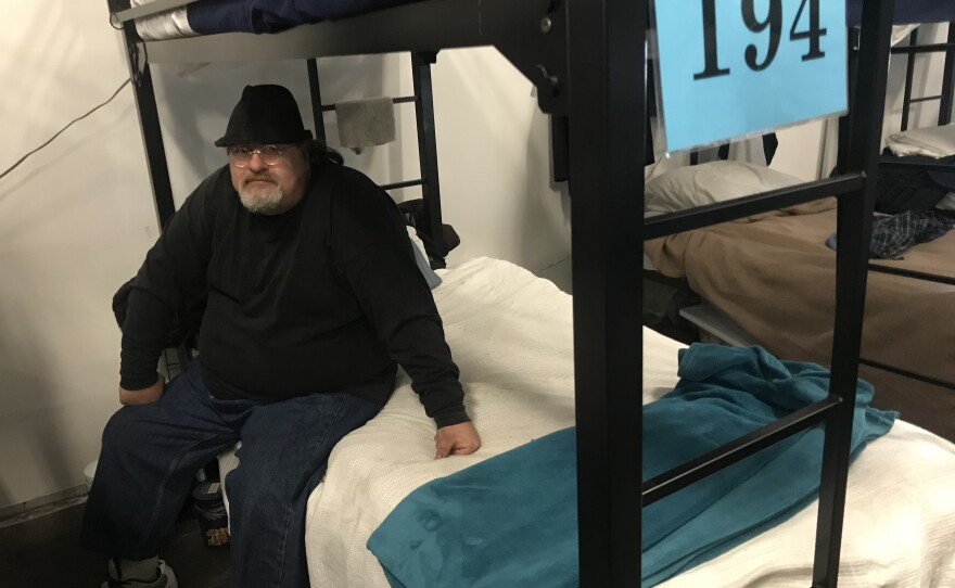 Joseph Lemaster, 49, sits on his assigned bed in a homeless tent shelter near downtown San Diego, Feb. 21, 2018.