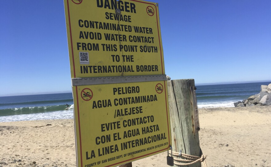 A surfer rides a wave in Imperial Beach in San Diego, Calif., Friday, March 2, 2018, behind a sign warning of the sewage-contaminated water from the Tijuana River Valley.