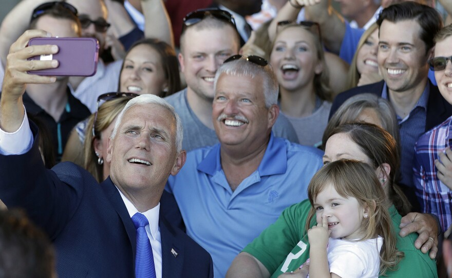 Republican vice presidential nominee Gov. Mike Pence of Indiana takes photos with supporters during a Welcome Home Rally on Saturday in Zionsville, Ind. Pence is a passionate advocate for school choice and state control over federal oversight.