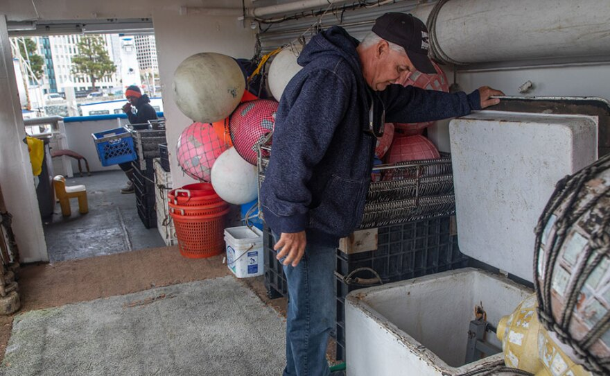 David Haworth looks into the supply hold of one of his fishing boats in San Diego's Tuna Harbor, March 18, 2020. The boat was scheduled to go out earlier in the day, but Haworth kept it in after hearing from buyers there would be no market for the fish.