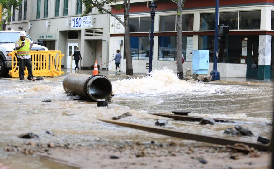 A worker stands by a water main break in downtown San Diego, June 15, 2015.