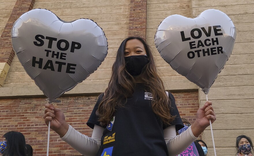 """Chinese-Japanese American student Kara Chu, 18, holds a pair of heart balloons decorated by herself for the rally """"Love Our Communities: Build Collective Power"""" to raise awareness of anti-Asian violence outside the Japanese American National Museum in Little Tokyo in Los Angeles, March 13, 2021."""
