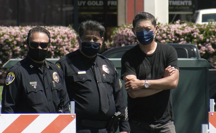 Two San Diego Police officers stand outside a parking lot next to business owner Michael Tu (right) in the Convoy District, April 8, 2021.