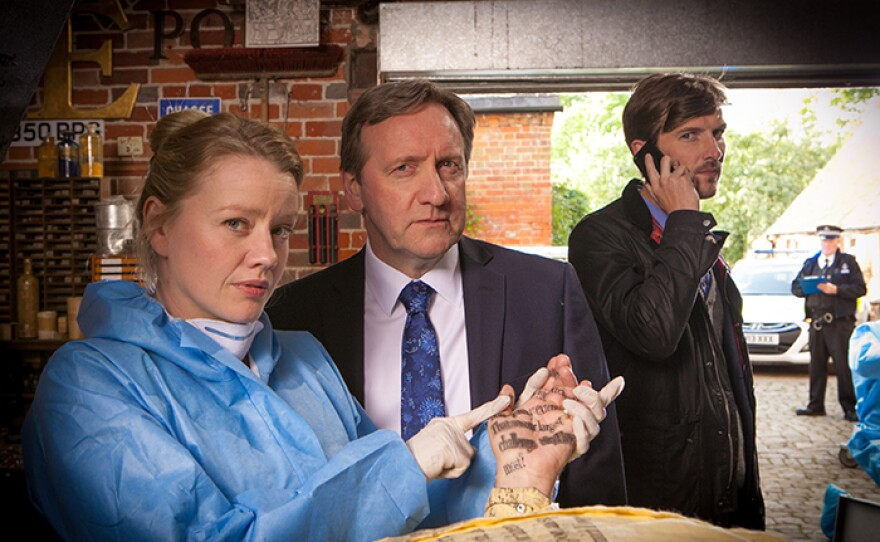 """Chief Pathologist Dr. Kate Wilding (Tamzin Malleson), Detective Chief Inspector John Barnaby (Neil Dudgeon) and Detective Sergeant Charlie Nelson (Gwilym Lee) in a scene from MIDSOMER MURDERS """"The Dagger Club."""" Can new dad Barnaby untangle a web of jealousy and obsession to find the killer?"""