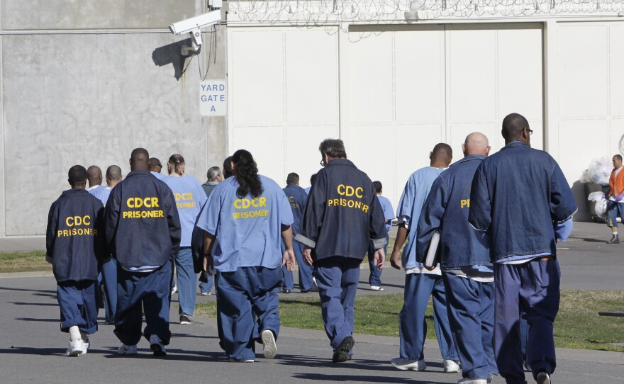 In this photo Feb. 26, 2013 file photo, inmates walk through the exercise yard at California State Prison Sacramento, near Folsom, Calif.