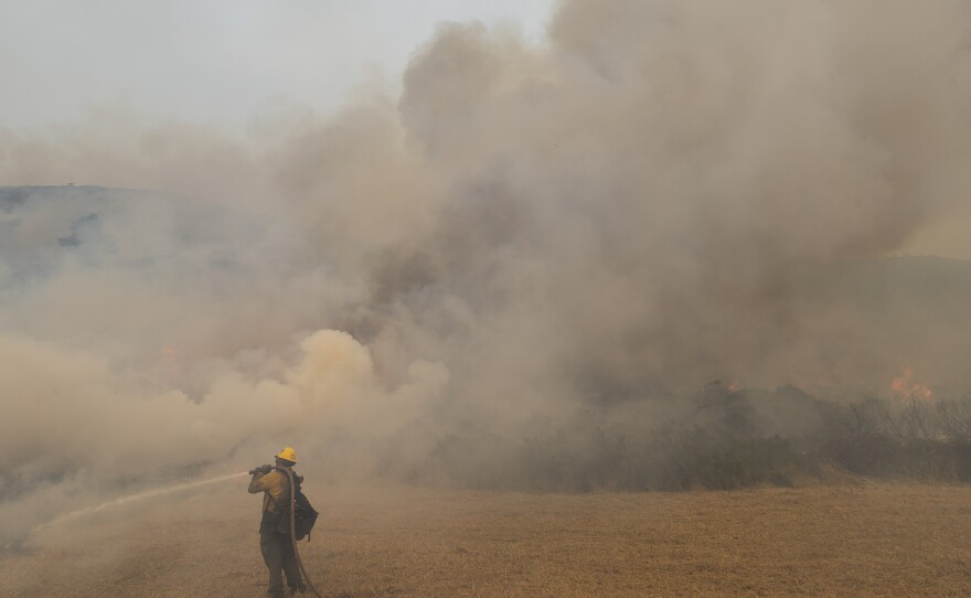A firefighter sprays water on a controlled burn while fighting the Dolan Fire near Big Sur, Calif., on Sunday. Millions of acres have burned in California and neighboring states this year.