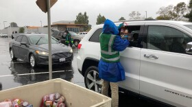 San Diego Food Bank workers distribute 25-lb packages of food to people in their cars at a pop-up food distribution site in Chula Vista, April 10, 2020.