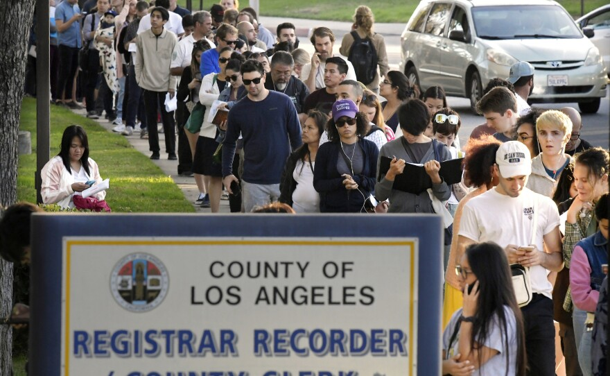 In this Nov. 6, 2018 file photo potential voters wait in long lines to register and vote at the Los Angeles County Registrar's office in Los Angeles.
