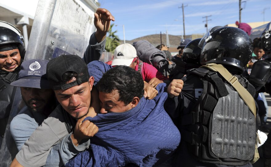 Migrants clash with Mexican police at the Mexico-U.S. border after getting past another line of Mexican police at the Chaparral crossing in Tijuana, Mexico, Sunday, Nov. 25, 2018, as they try to reach the U.S.