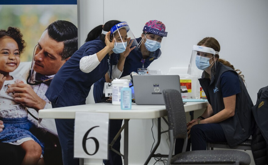 UC Davis Medical Center nurses, from left, Analyn Corpuz, Raenne Takara and Heather Donaldson review the process of inoculating with the Pfizer-BioNTech COVID-19 vaccine, Tuesday, Dec. 15, 2020 in Sacramento, Calif.