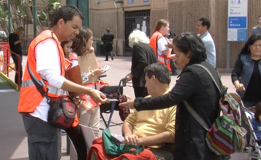 Immigration activists give people crossing the border informative pamphlets about their rights, May 13, 2015.