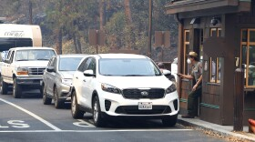 Park Ranger Alex Martinez passes maps out and directs visitors at the Hwy 140 gate as Yosemite National Park reopens after a three week closure from smoke and fires that led to most tourists canceling their trips Tuesday, Aug. 14, 2018 in Yosemite, Calif.