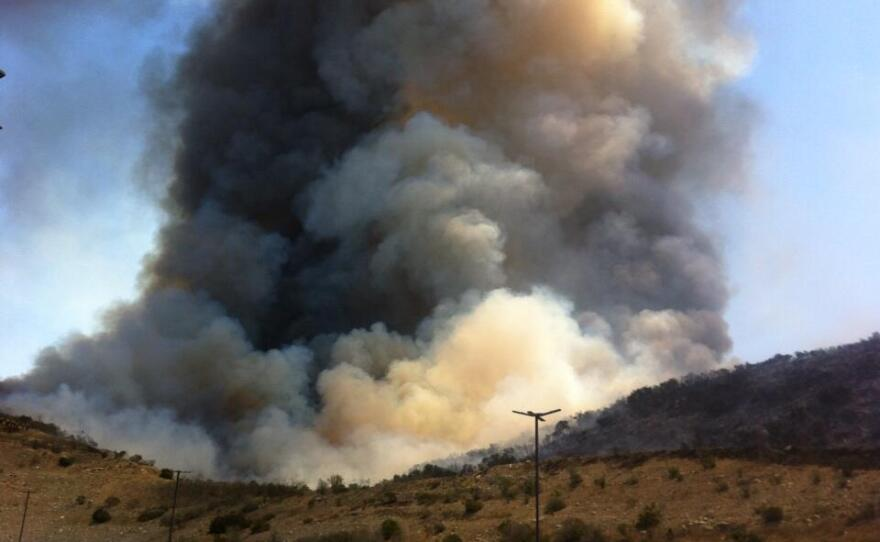 A large plume of white and black smoke rises from a hillside brush fire in San Marcos.