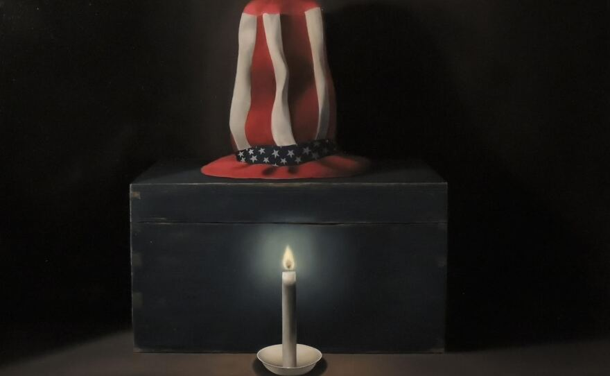 """""""The Flame,"""" a painting by San Diego artist Mark Bryce, features an Uncle Sam hat sitting on a blue box with a dimly lit candle in the foreground."""