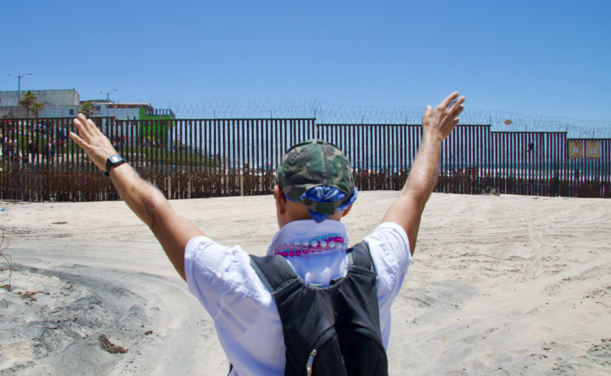 At a silent March in June, 2021 meant to pressure U.S. Border Patrol to open the gates at Friendship Park, a protestor raises his arms to greet protestors on the Tijuana side of the U.S.-Mexico Border Fence.