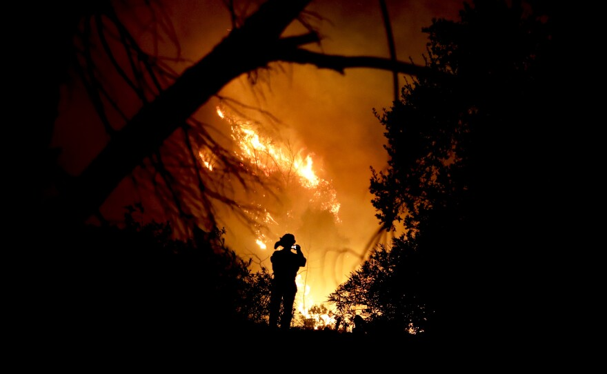 A firefighter takes a cell phone picture during a wildfire in Montecito, Calif., Saturday, Dec. 16, 2017.