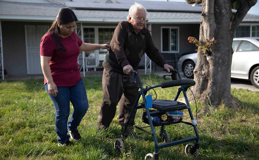 Cristina Hernandez walks with her dad Francisco Rios, 91, across the lawn at her Pomona home in this undated photo. She has been his primary caregiver for 15 years.