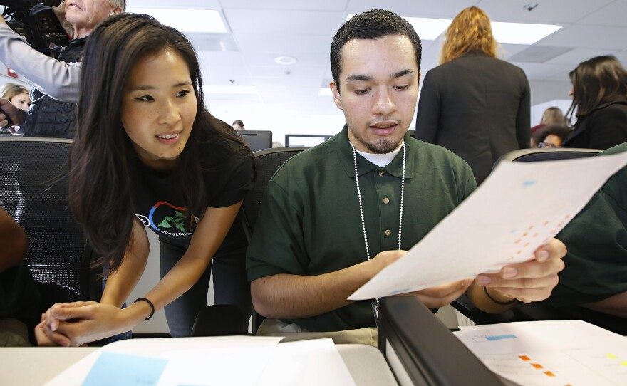In this Jan. 22, 2019, file photo, Ashley Ma, left, a senior digital visual designer with Google, reviews a website design done by Osvaldo Moreno Jr., a youth offender at the O.H. Close Youth Correctional Facility, in Stockton, Calif.