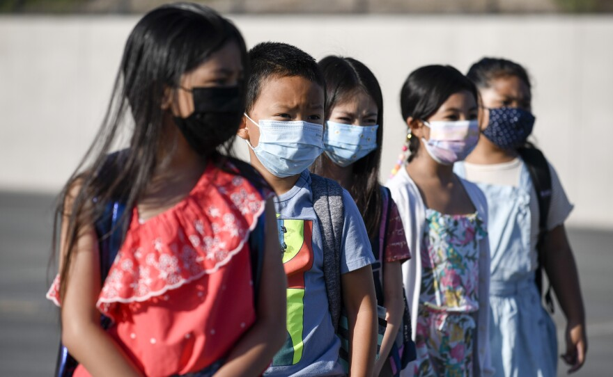 Masked students wait to be taken to their classrooms at Enrique S. Camarena Elementary School in Chula Vista, California, July 21, 2021.