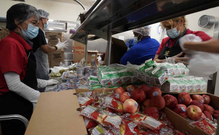Los Angeles Unified School District food service workers from left, Tomoko Cho, Aldrin Agrabantes, April Thomas, and Marisel Dominguez, pre-package hundreds of free school lunches in plastic bags on Thursday, July 15, 2021, at the Liechty Middle School in Los Angeles.