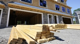 In this June 24, 2021 photo, lumber is piled at a housing construction site in Middleton, Mass.