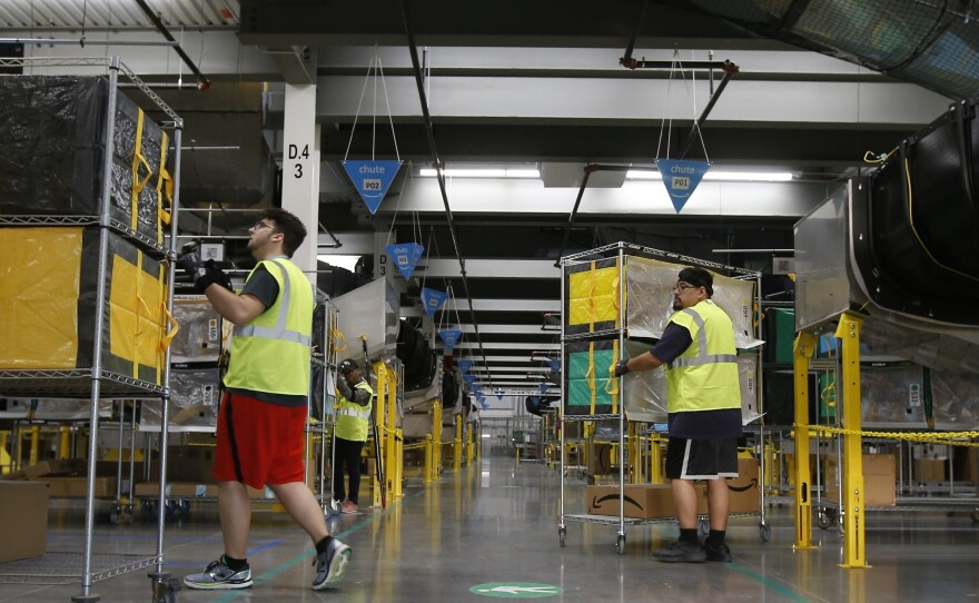 In this Dec. 17, 2019, file photo, Amazon workers move containers to delivery trucks at an Amazon warehouse facility in Goodyear, Ariz.