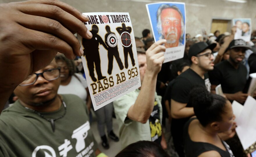 """Protestors shouting """"black lives matter"""" hold up photos of people they claim are the victims of police violence as they block the hallway outside the governors office while successfully demanding the passage of AB953, in Sacramento, Calif.,  Sept. 2, 2015."""