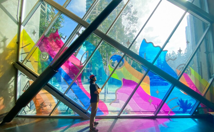 """Artist Regan Russell stands in the colorful shadow of """"Energized,"""" seen in this undated photo from inside the New Children's Museum."""