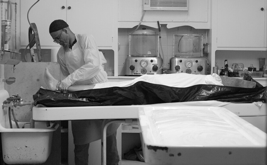 Funeral worker Hanif Muhammad prepares a body he's received for washing to start a janazah, the Islamic ritual of preparing a body for burial.