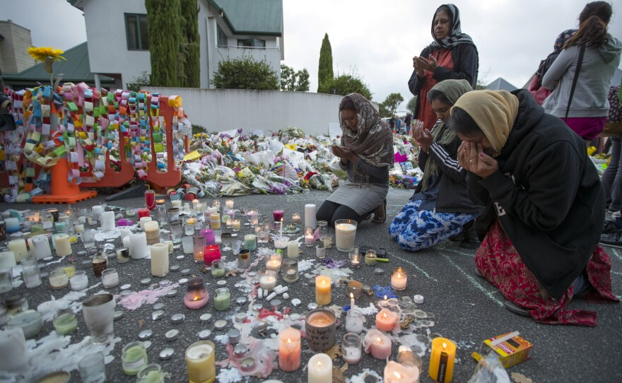 People mourn at a makeshift memorial site near the Al Noor mosque in Christchurch, New Zealand, Tuesday, March 19, 2019.